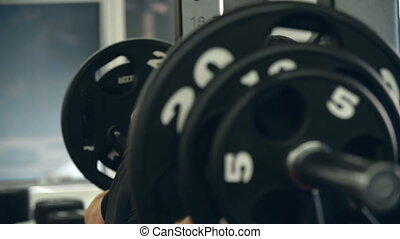35 Kilos - Close up of three barbell plates while sportsman...