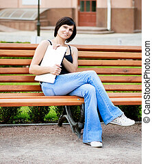 brunette girl sitting on a sunny day on a bench in the park with laptop in her hands