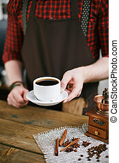 Cup of black coffee - Barista holding cup of black coffee...