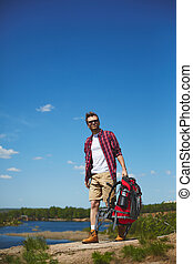 Man traveling - Young traveler with backpack walking down...
