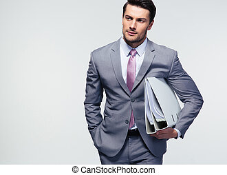 Young confident businessman holding folders over gray...