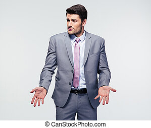 Businessman shrugging shoulders over gray background Looking...
