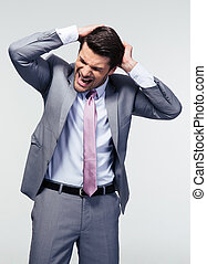 Portrait of a frustrated businessman over gray background