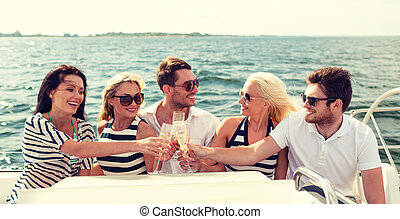 smiling friends with glasses of champagne on yacht -...