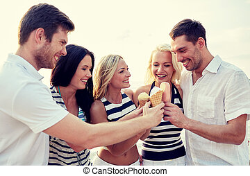 smiling friends eating ice cream on beach - summer,...