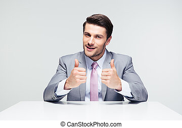 Businessman sitting at the table with thumbs up - Handsome...