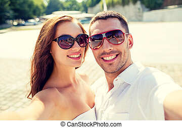 smiling couple wearing sunglasses making selfie - love,...