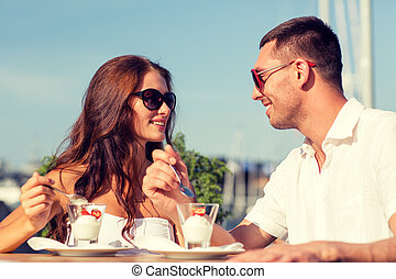 smiling couple eating dessert at cafe - love, dating, people...