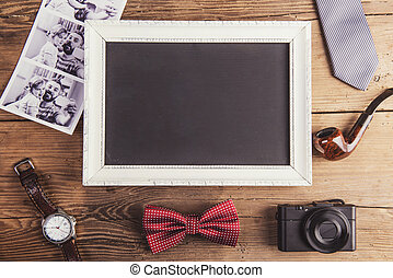 Picture frame, instant photos and various objects on wooden...