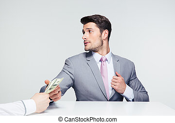 Businessman taking bribe - Businessman sitting at the table...