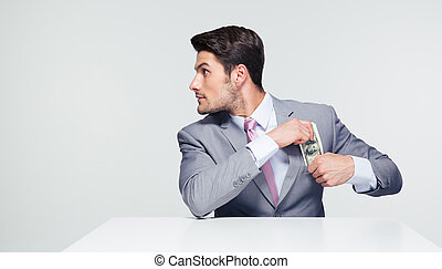 Businessman putting money in pocket - Young businessman...