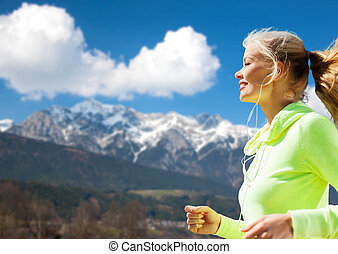 happy young woman with earphones jogging outdoors - fitness,...