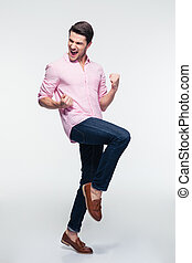 Laughing young businessman celebrating his success over gray...