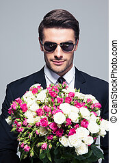 Businessman in sunglasses holding flowers - Handsome...