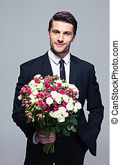 Businessman holding flowers - Handsome businessman holding...
