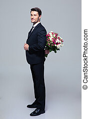 Businessman hiding bouquet of flowers behind his back over...