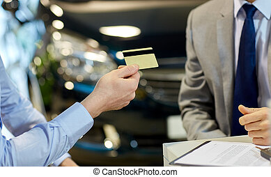 customer giving credit card to car dealer in salon - auto...