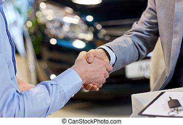 close up of male handshake in auto show or salon - auto...