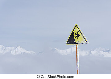 danger steep cliff mountain sign, mountains and cloudy sky