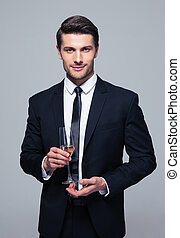 Businessman holding glass of champagne - Happy businessman...