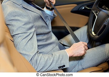 close up of man fastening seat safety belt in car