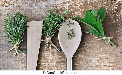 aromatic herbs on wooden background with spoons