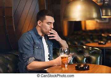 man drinking beer and smoking cigarette at bar - people and...