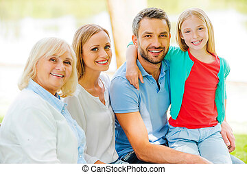 Enjoying time with family. Happy family bonding to each other and smiling while sitting outdoors together
