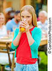 Enjoying fresh juice. Cute little girl drinking orange juice and smiling while her family sitting at the dining table in the background