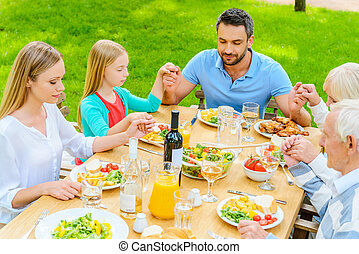Praying before dinner. Top view of family of five people holding hands and praying before dinner while sitting at the table outdoors