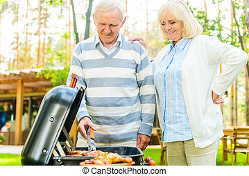 Enjoying barbeque together Happy senior couple barbecuing...