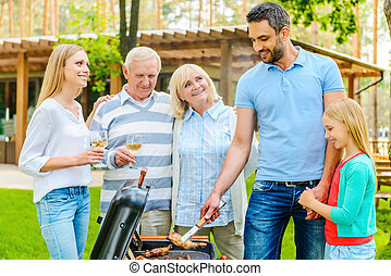 Family barbeque. Happy family of five people barbecuing meat...