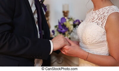 young newlyweds couple holding hands with rings and wedding...