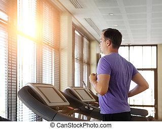 Man training on a treadmill in a sport centre