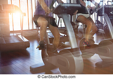 Couple training on a treadmill in a sport centre