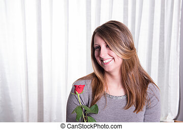 Portrait pretty young woman in love  with rose