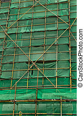Construction scaffolding and green debris netting abstract...