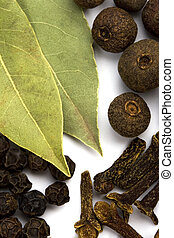 cooking herbs. bay leafs, cloves and black pepper closeup on...