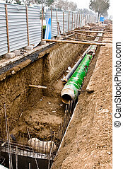 Metal pipes with thick heat isolation lieing in the trench -...