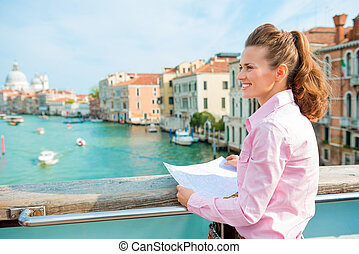 Smiling woman in profile holding map on bridge above Grand...