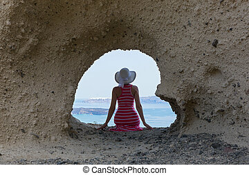 Woman sitting on rocks , near cave in the shape of a heart -...