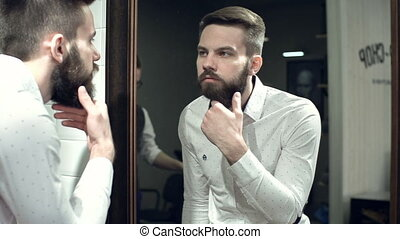 Beard Style - Close up of man looking in the mirror and...