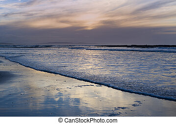 reflections and calm waves crashing onto the beach at...