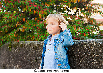 Outdoor portrait of a cute little boy, wearing denim jacket
