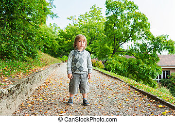 Outdoor portrait of a cute little boy wearing grey pullover...