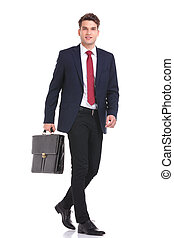Side view of a young business man holding a brief case