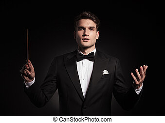handsome man conducting an orchestra.