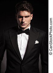 elegant man wearing a black tux. - Portrait of a handsome...