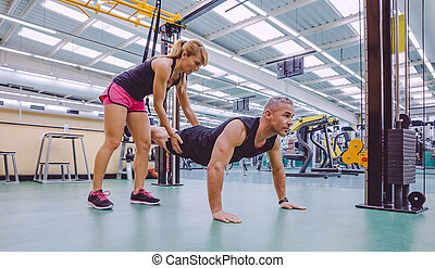 Personal trainer teaching to man in suspension training -...