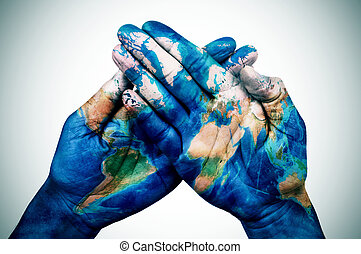 man hands patterned with a world map (furnished by NASA) -...